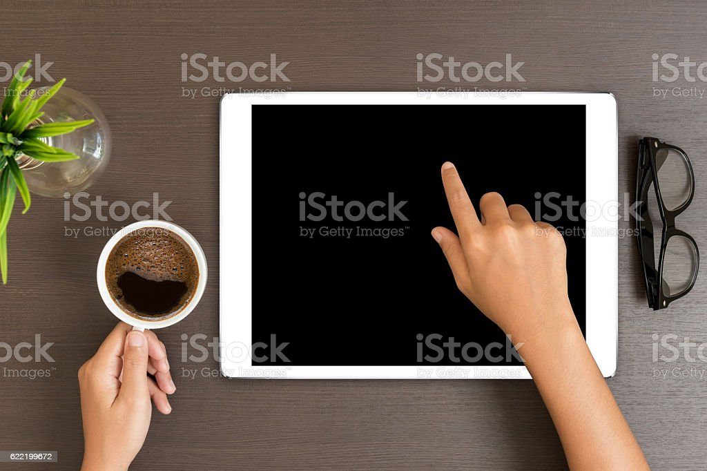 hand use white tablet on desk table top view stock photo