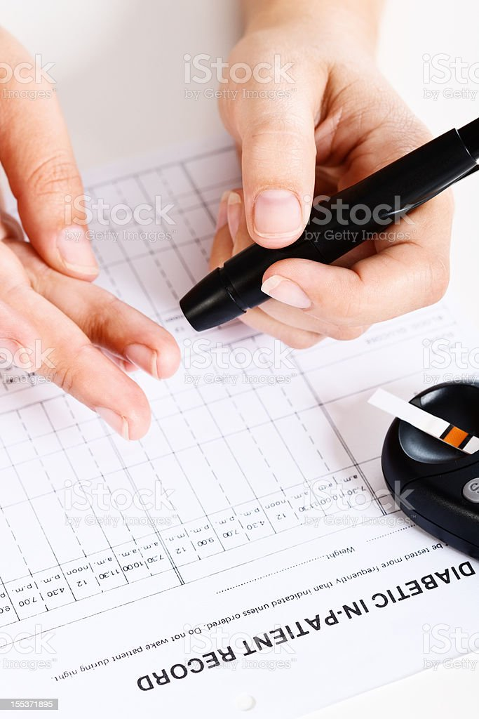 Hand uses automatic lancet to draw blood stock photo