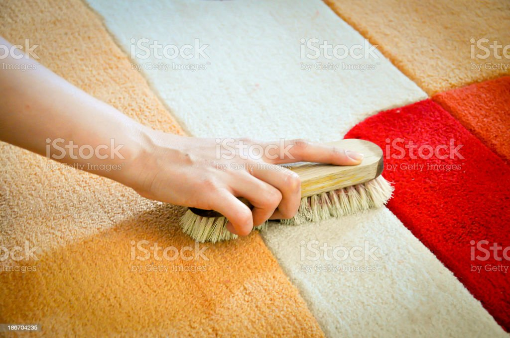 A hand using a brush to clean a carpet stain stock photo