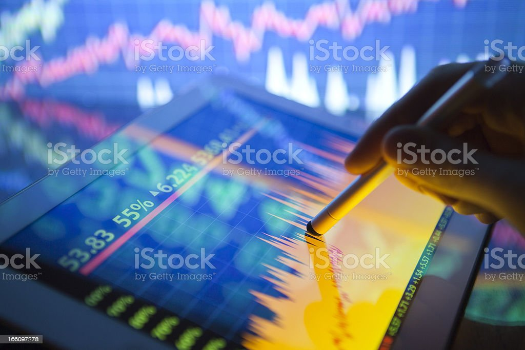 A hand using a digital tablet showing stock fluctuations royalty-free stock photo