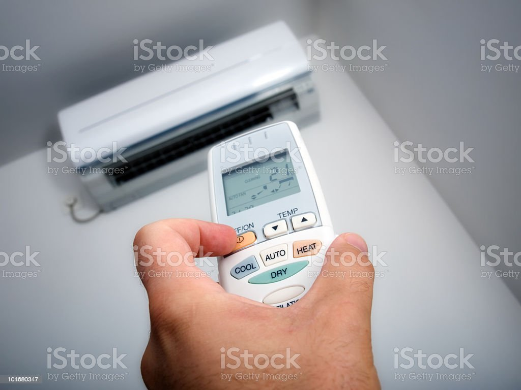 Hand using a remote control to turn on the air conditioner stock photo