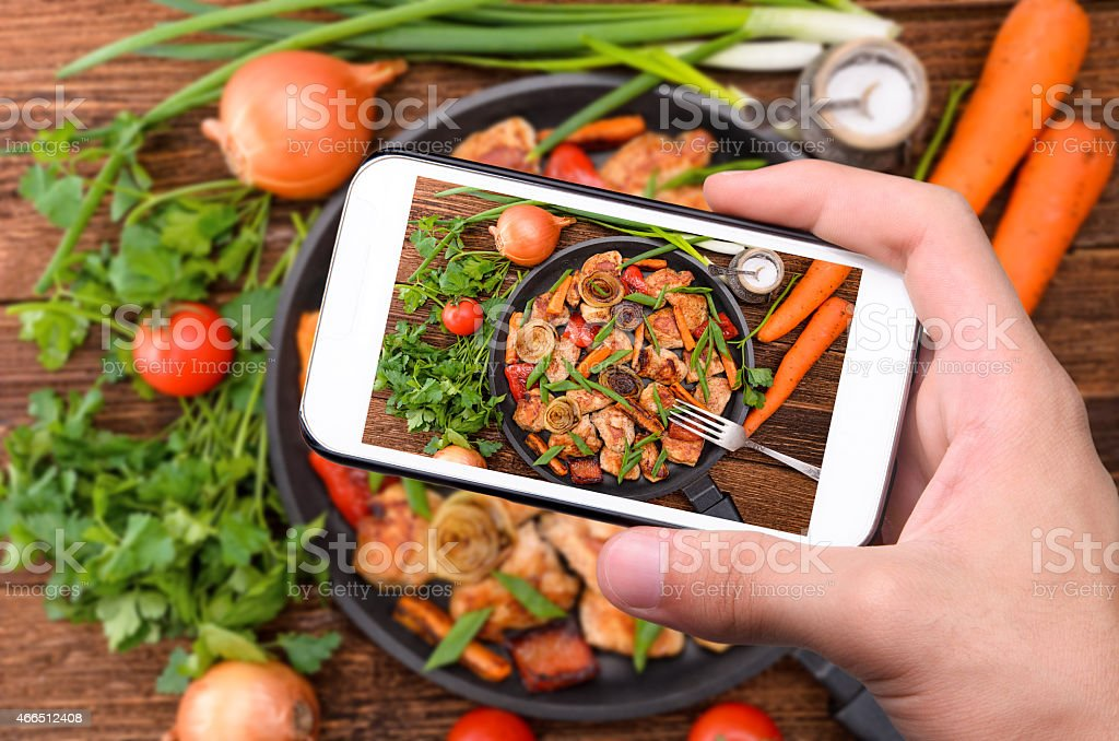 Hand using a smartphone to take photo of their meal stock photo