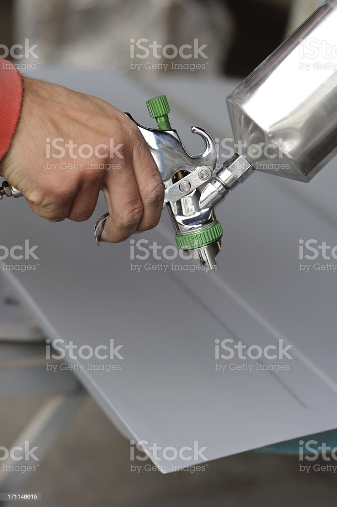 A hand using a spray gun to hand spray car parts. royalty-free stock photo