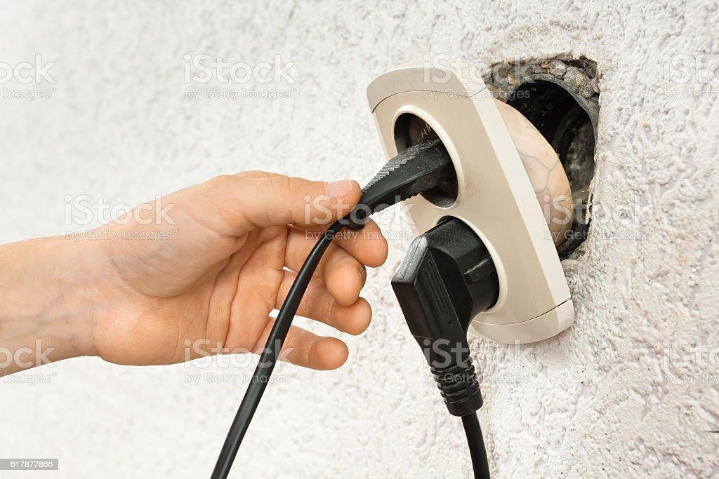 hand using broken electric socket stock photo