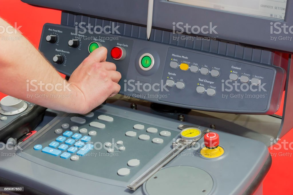 Hand using control panel of a cnc machine stock photo