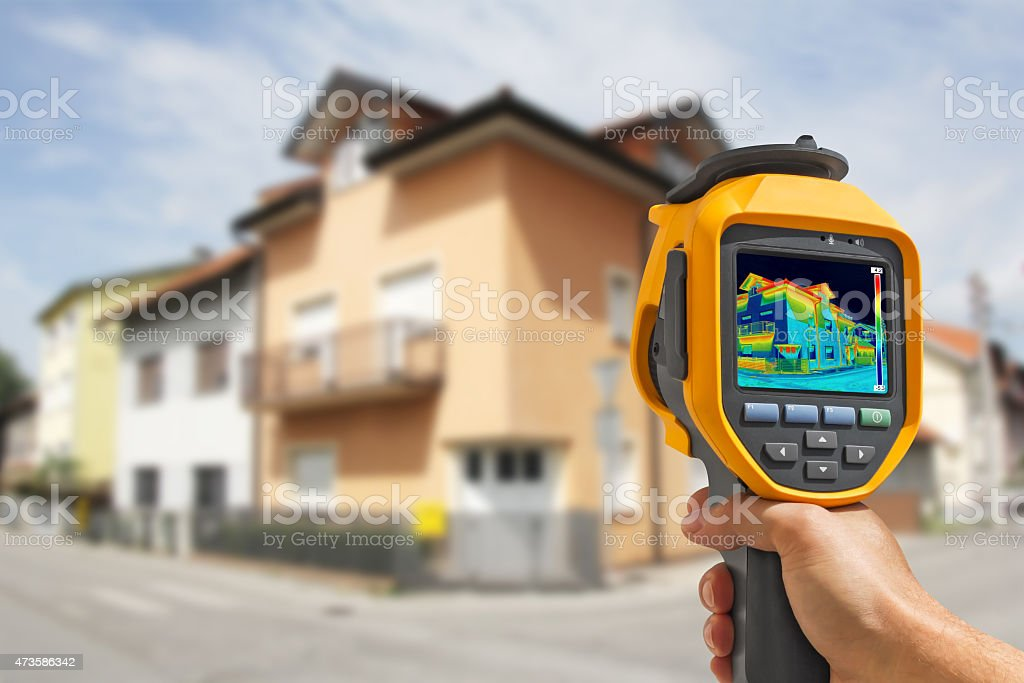 Hand using equipment to record Heat Loss at the House stock photo