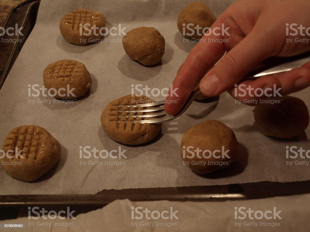 Hand using fork tines to press peanut butter cookies stock photo