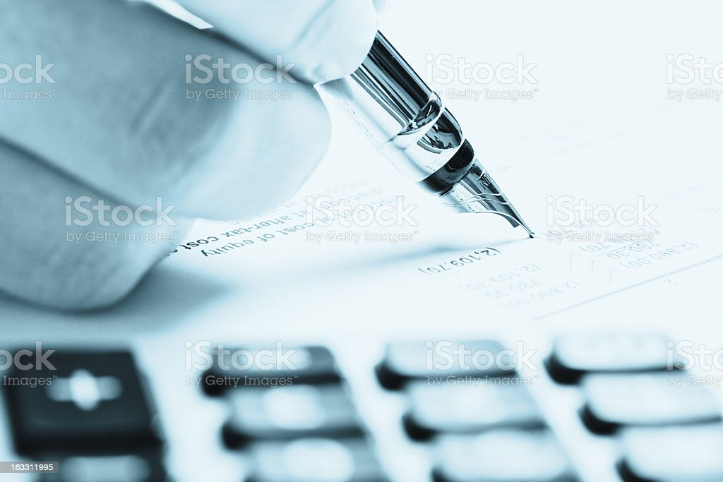 Hand using fountain pen and calculator to check document royalty-free stock photo