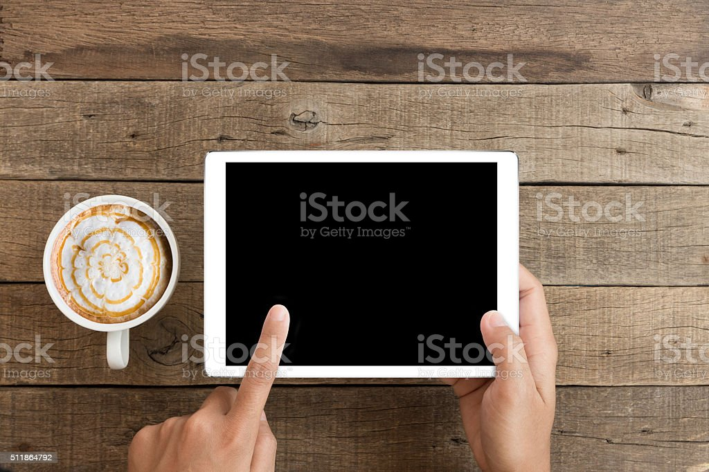 hand using mockup tablet on wood with clipping path display stock photo