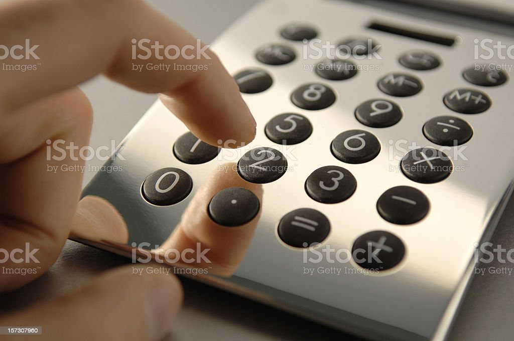 Hand Using Silver Calculator stock photo