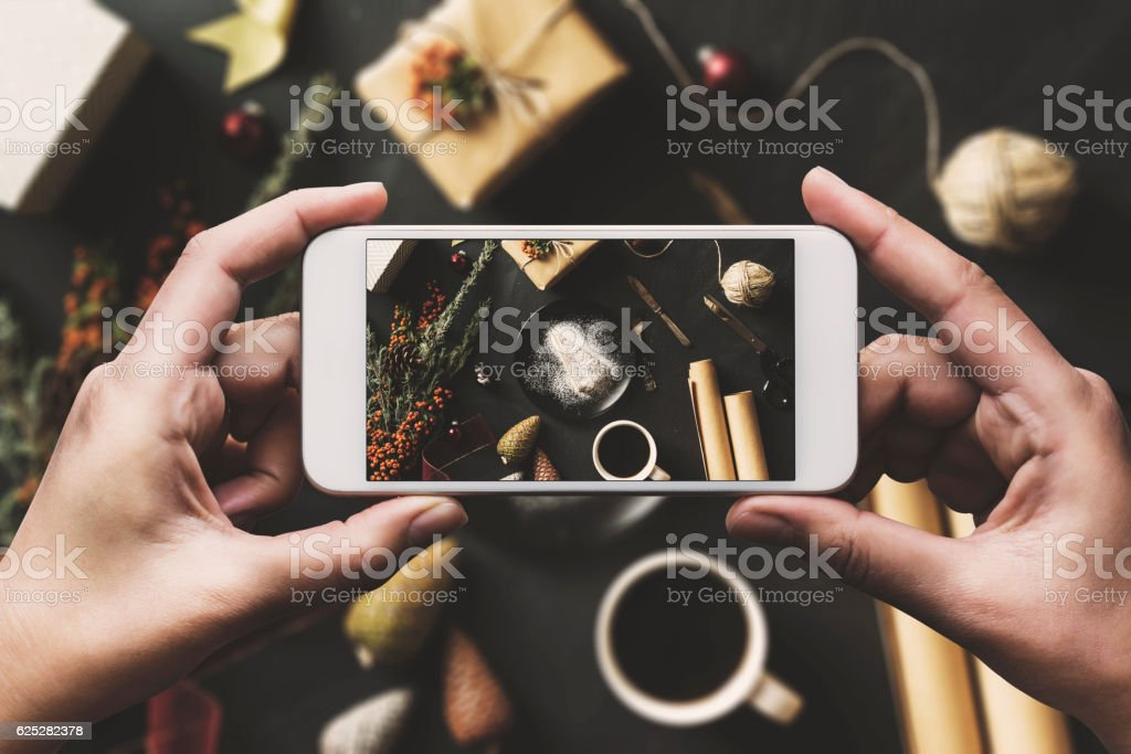Hand using smartphone, sharing Christmas flat lay on social media stock photo