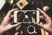 Hand using smartphone, sharing Christmas flat lay on social media