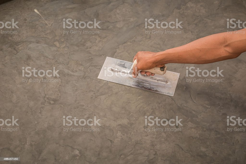 hand using steel trowel to finish Polished wet concrete surface stock photo