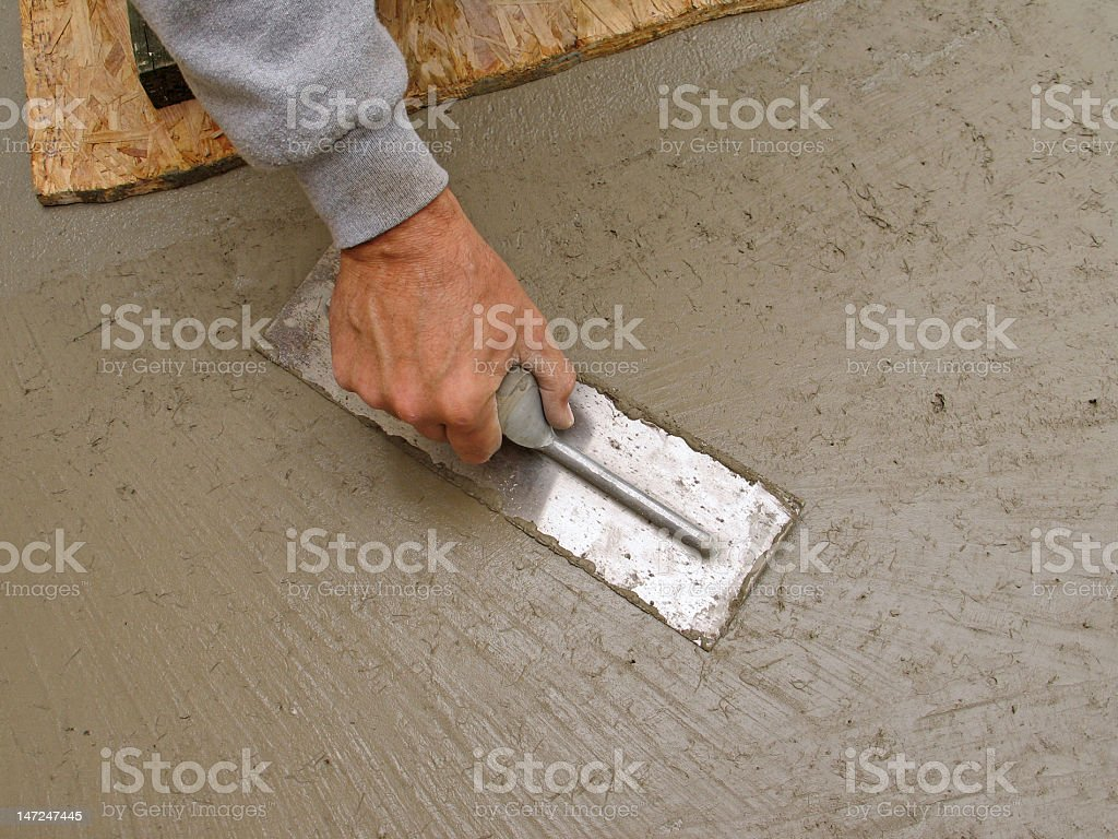 Hand using trowel to finish concrete slab royalty-free stock photo