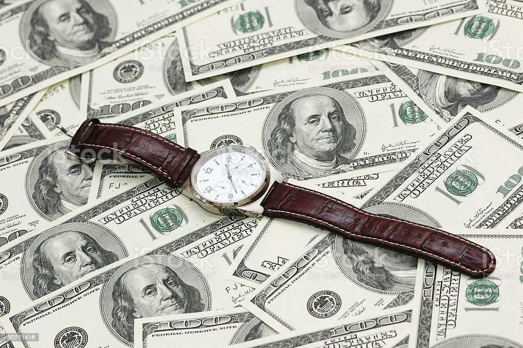 Hand watch over the hundred dollar bank notes royalty-free stock photo