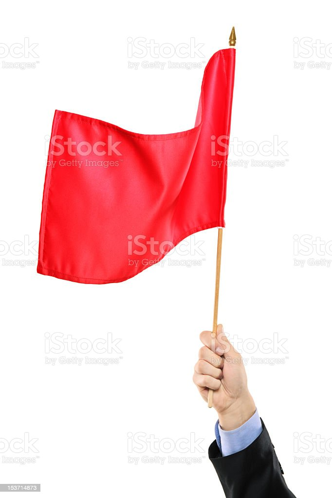 A hand waving a red flag on a white background stock photo