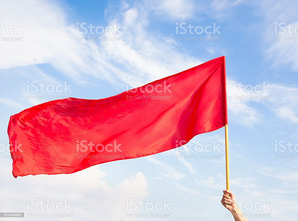 Hand waving a red flag with blue sky background stock photo