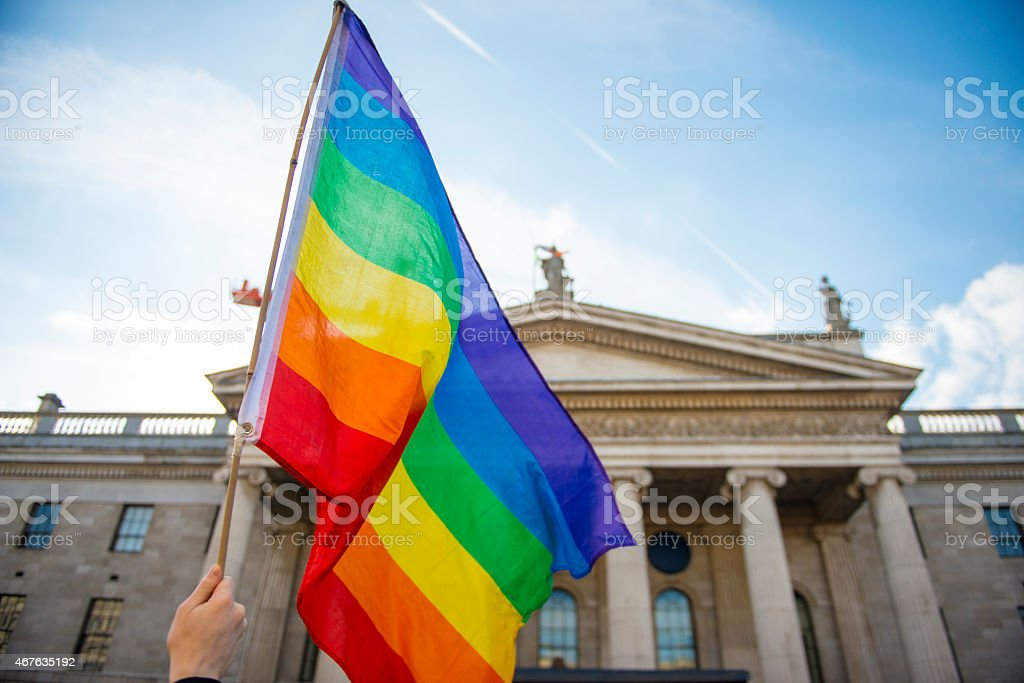 Hand waving gay pride flag in front of government building stock photo