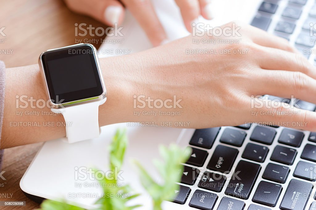 Hand wearable apple watch typing on laptop stock photo