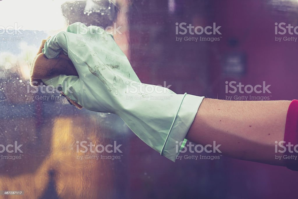 Hand wearing rubber glove is cleaning windows stock photo