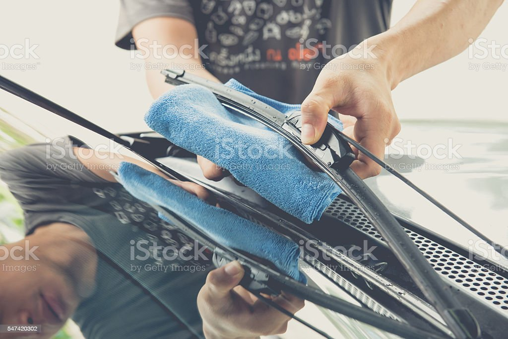 Hand wipe the windscreen wiper with cloth stock photo