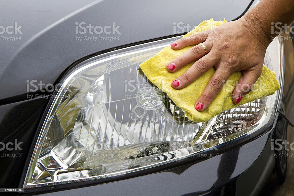 Hand wiping car headlight clean  stock photo