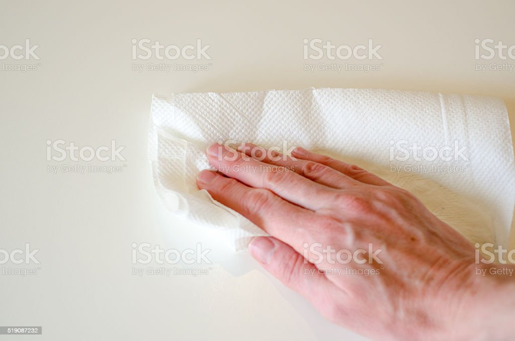 hand wiping white table with white kitchen paper stock photo
