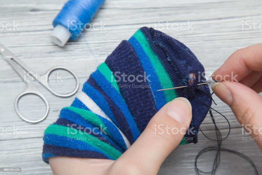 Hand with a needle and thread darning a sock. Sewing works. Handmade. Womanly hobby. stock photo