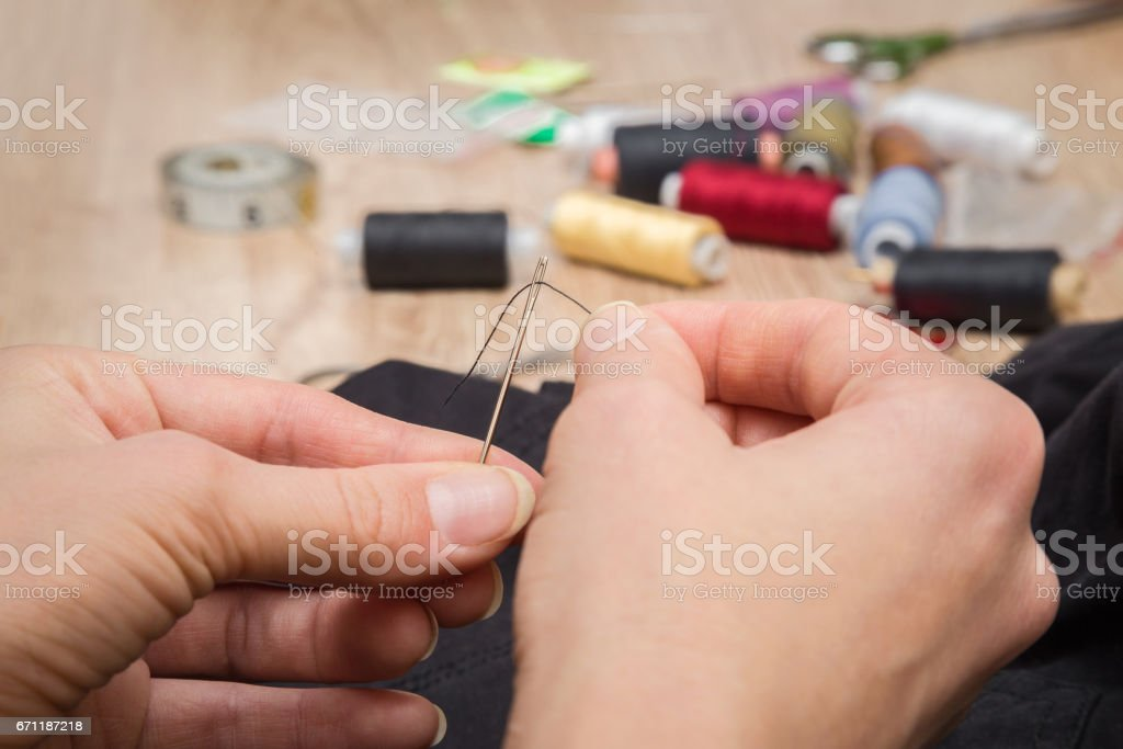 Hand with a needle and thread sewing clothes. Handmade. Womanly hobby. stock photo