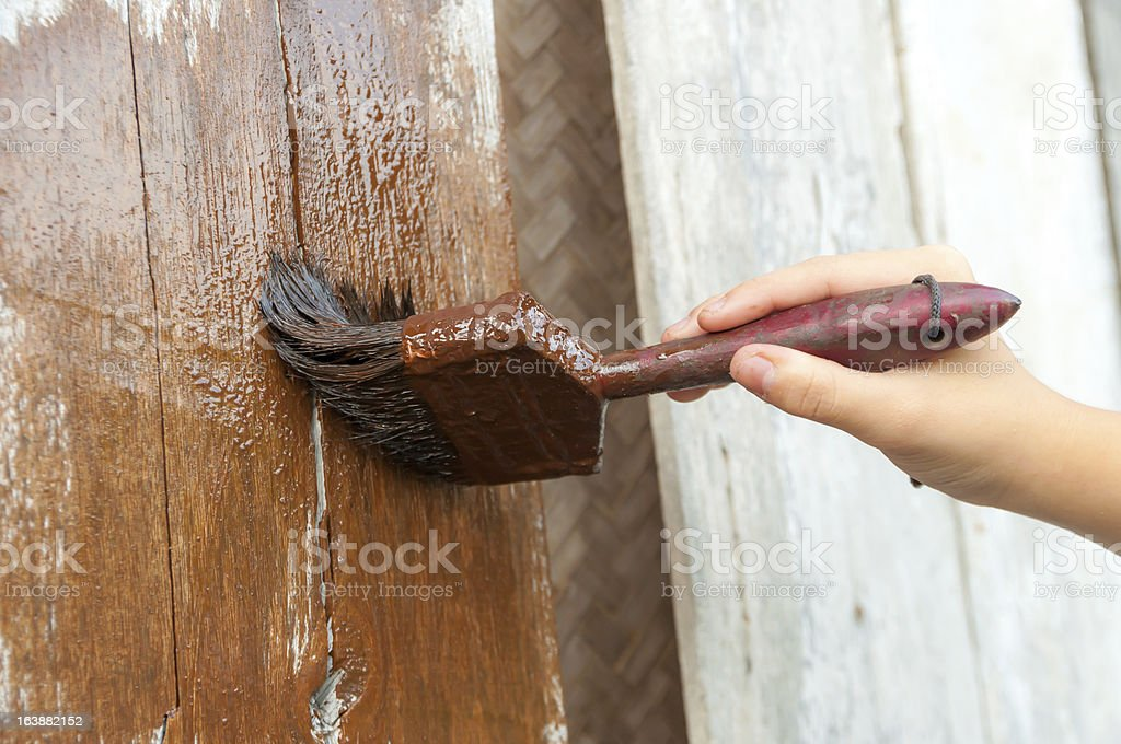 hand with a paint brush painting wooden wall royalty-free stock photo