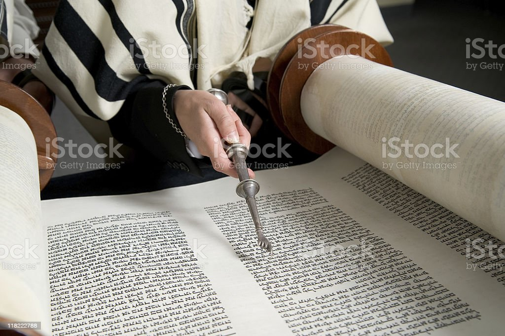 Hand with a silver pointer reading the Torah stock photo