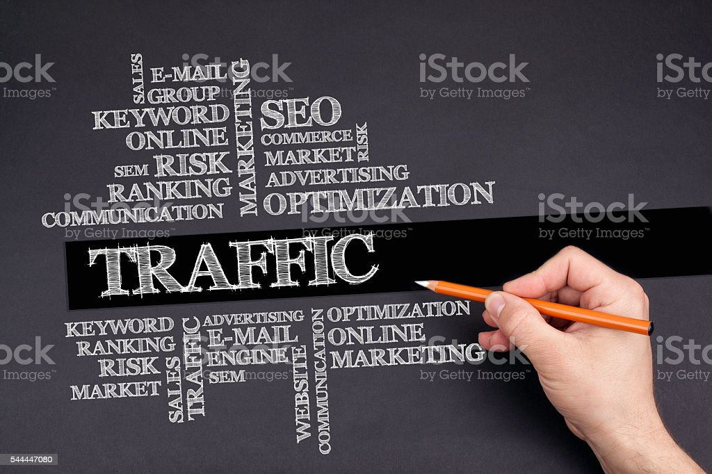 Hand with a white pencil writing: Traffic word cloud stock photo