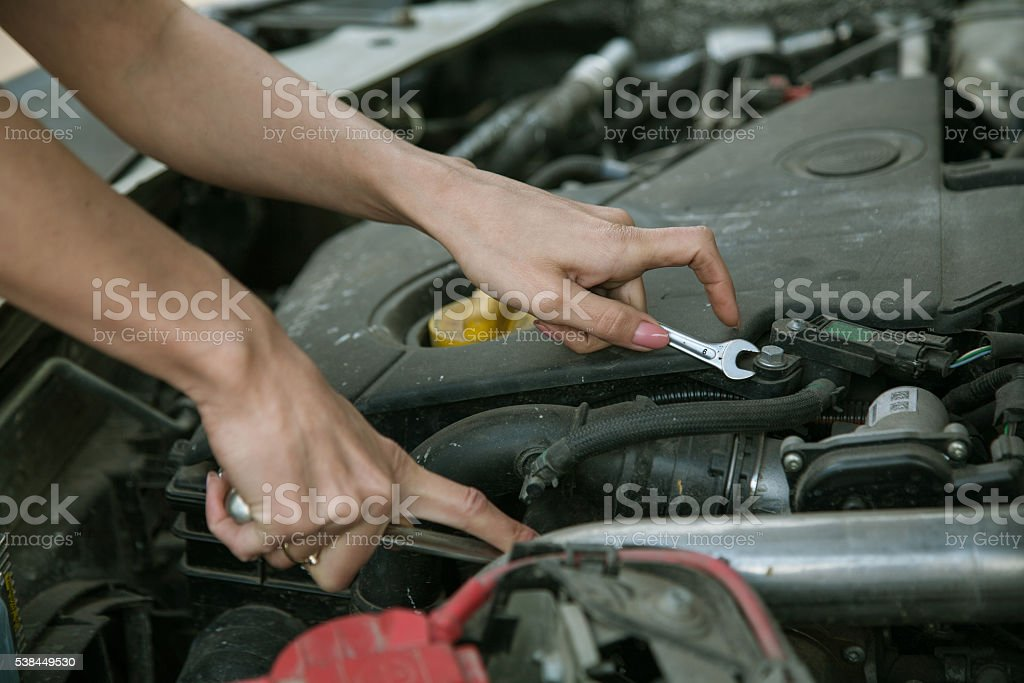 hand with a wrench under the hood of the car stock photo