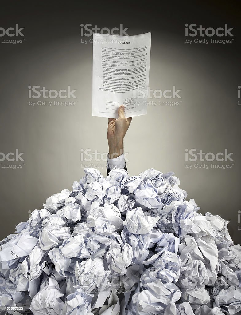 Hand with agreement reaches out from heap of papers royalty-free stock photo