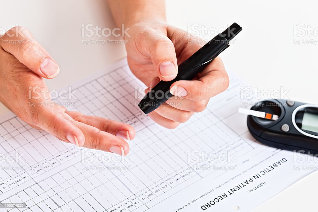 Hand with automated device to draw blood and glucometer stock photo