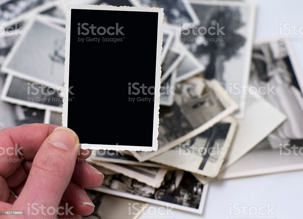 Hand with blank vintage photo among other photos in the back royalty-free stock photo