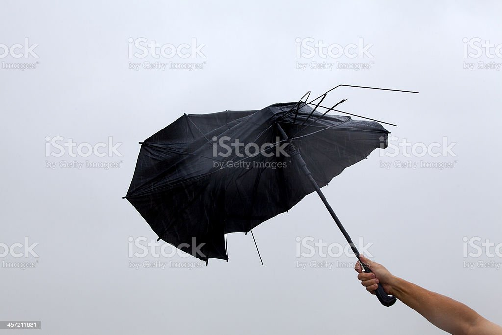 Hand with Broken Black Umbrella stock photo