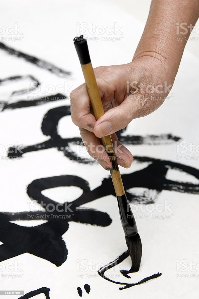 Hand with brush painting Chinese calligraphy stock photo