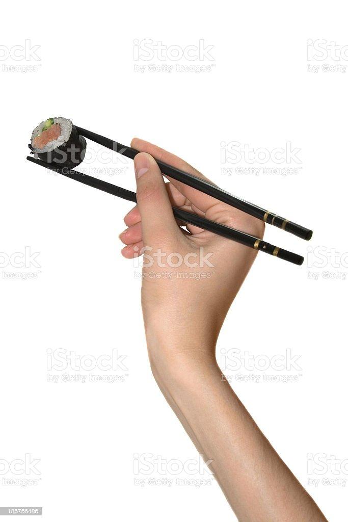 Hand with chopstick takes japanese sushi on white background royalty-free stock photo