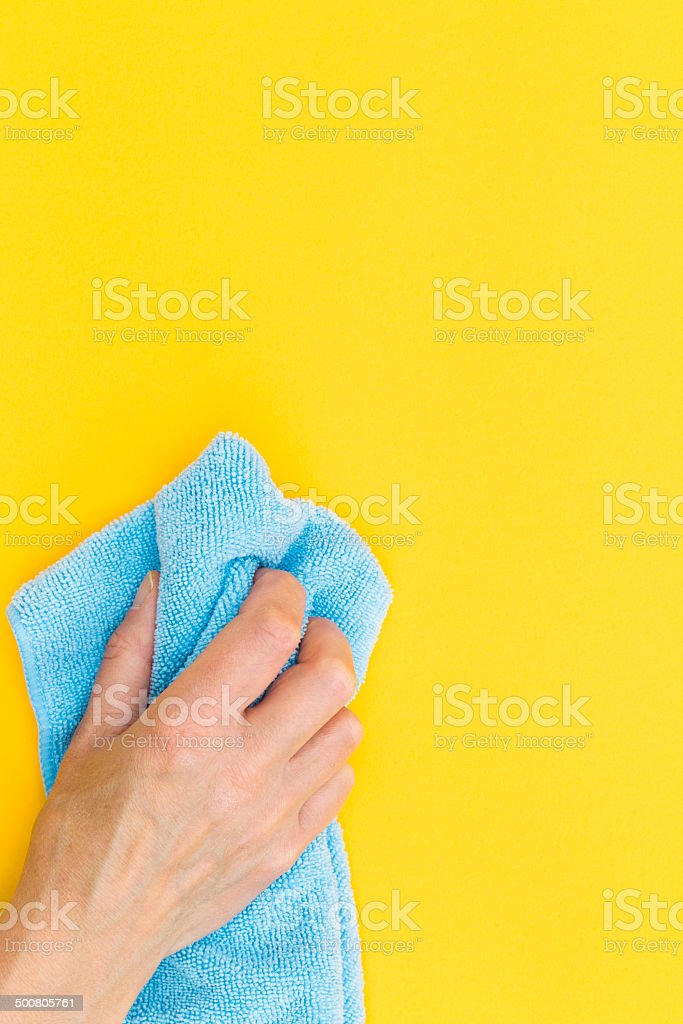 Hand with cloth cleaning a board stock photo