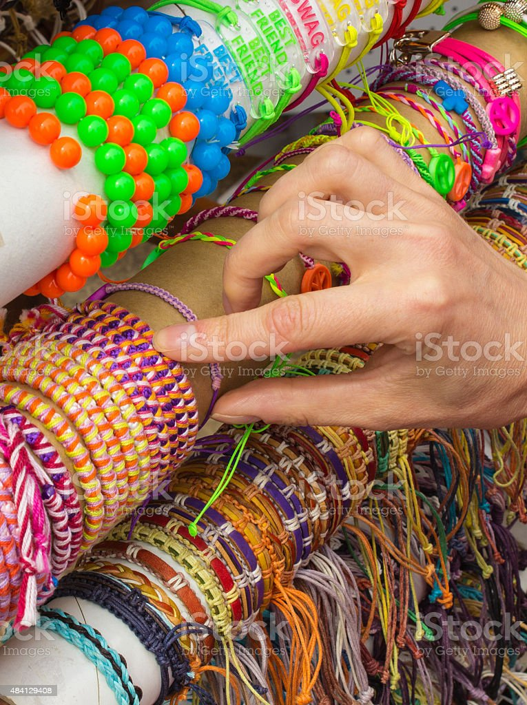 Hand with colorful bracelets on stall at the bazaar stock photo