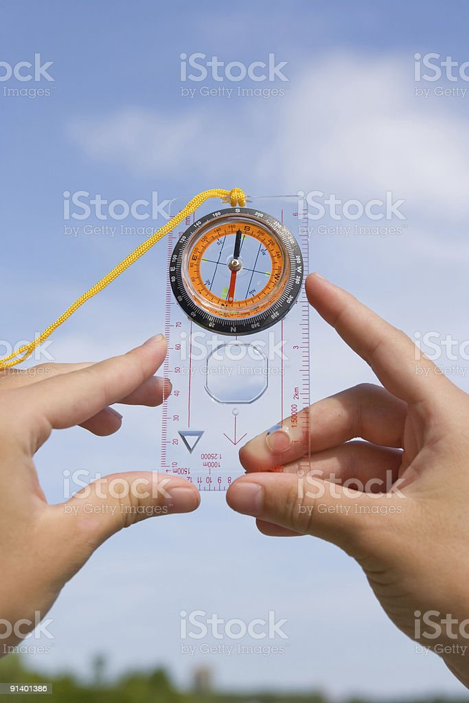 hand with compass on background sky stock photo