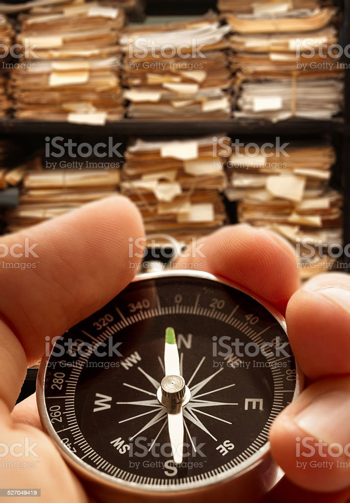 Hand with compass on paper documents stock photo