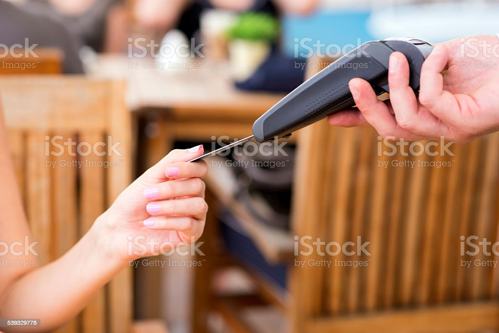 Hand with credit card swipe through terminal stock photo