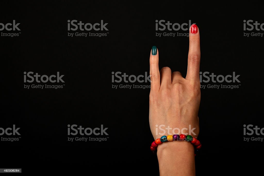 Hand with devil horns and colorful beads isolated on black royalty-free stock photo