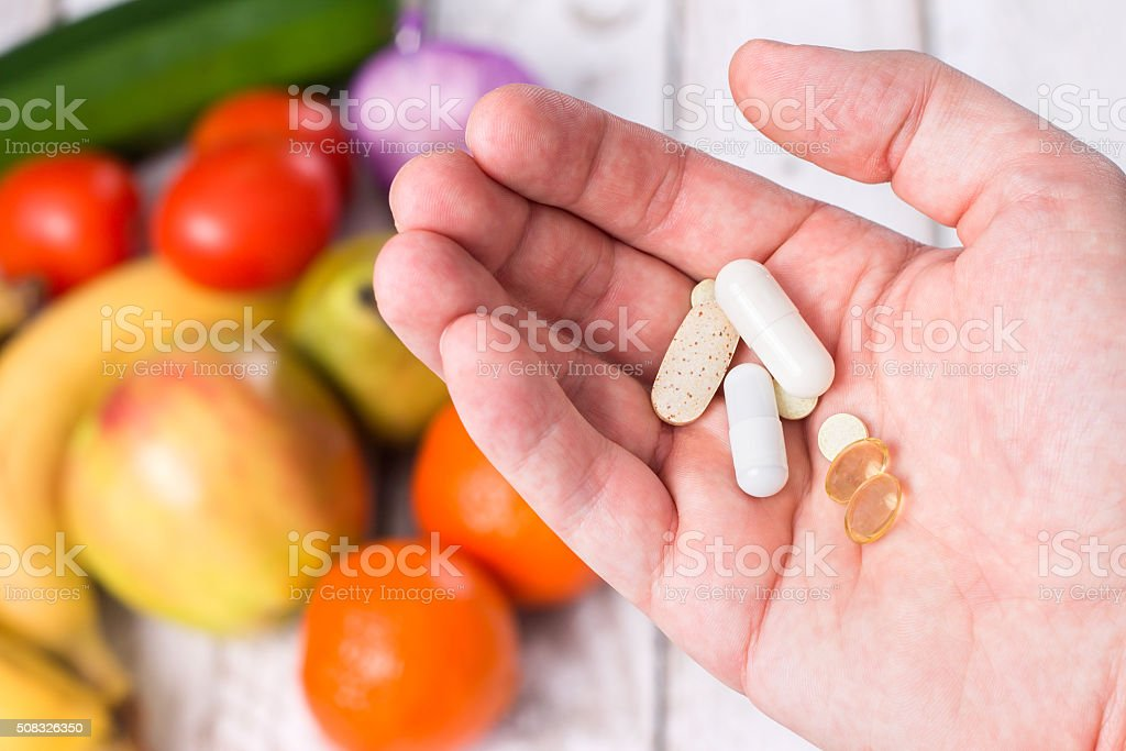 Hand with dietary supplements on fruity background stock photo