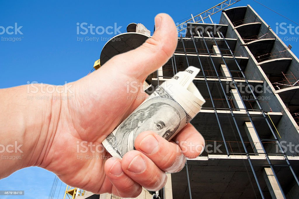 Hand with  dollars against the house under construction stock photo