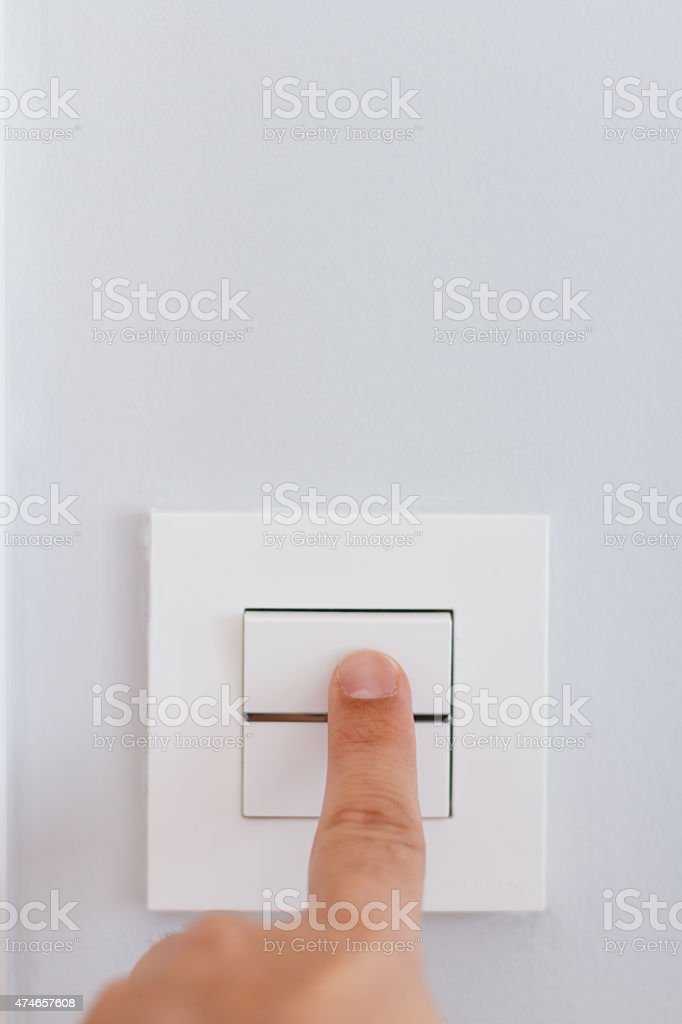 Hand with finger on light switch stock photo