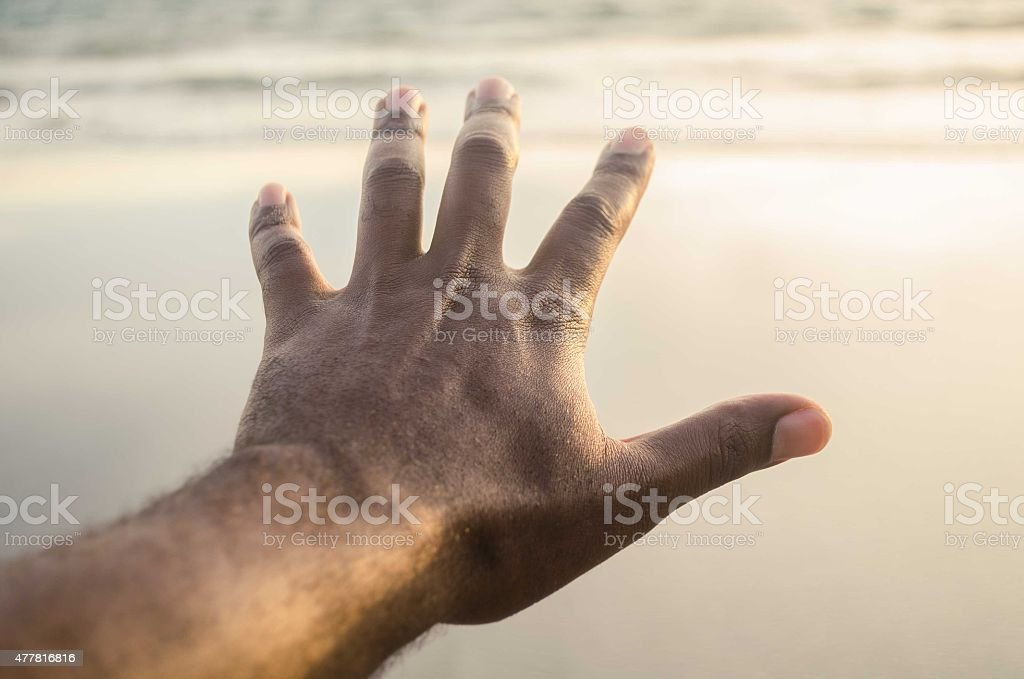 hand with fingers outstretched outdoors stock photo