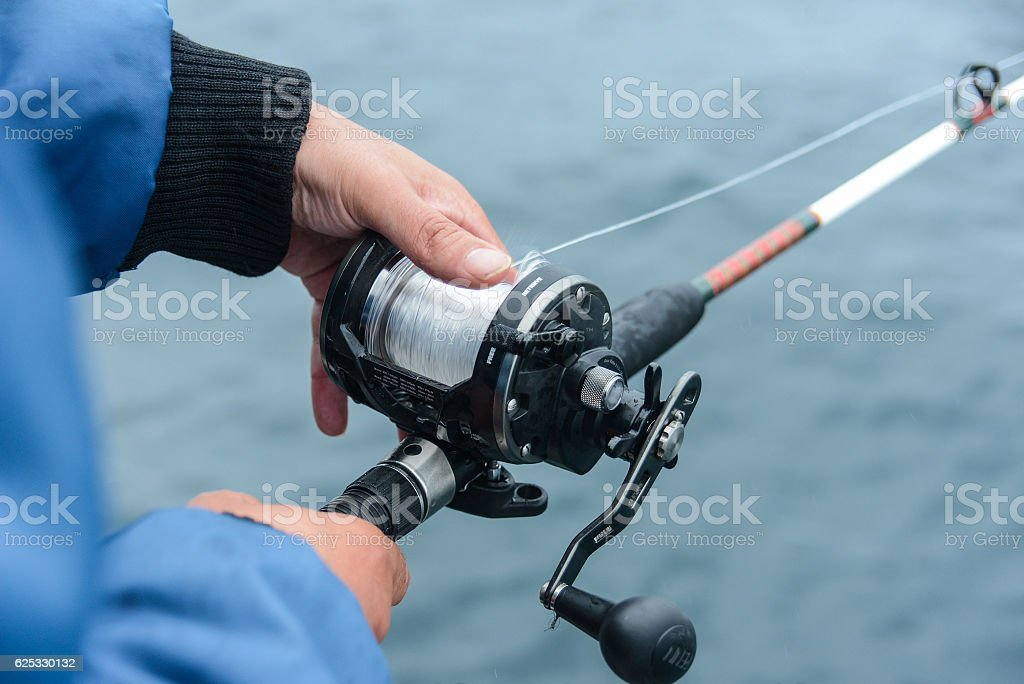hand with fishing rod on a boat stock photo